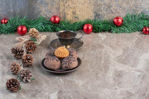 Teller mit keksen, eine tasse tee, ein bündel tannenzapfen und ein kranz auf marmor.