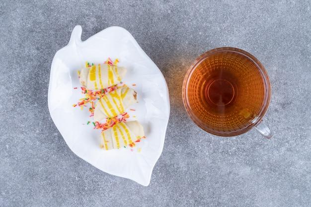 Teller mit keksen mit tasse tee auf marmoroberfläche