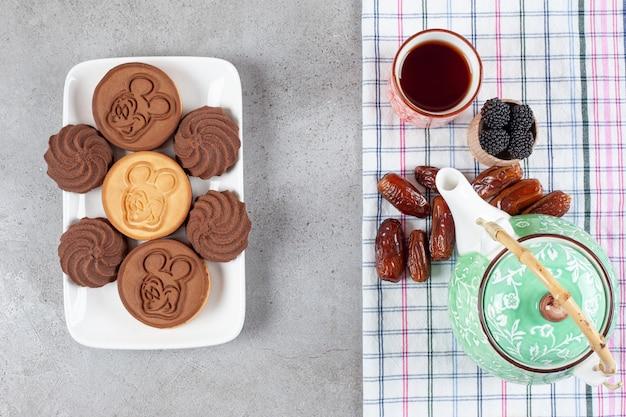 Teller mit keksen neben verzierter teekanne, datteln, einer tasse tee und einer schüssel teeblätter auf marmorhintergrund. hochwertiges foto