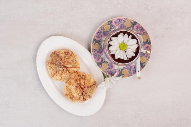 Teller mit keksen und einer tasse tee auf weißem tisch.