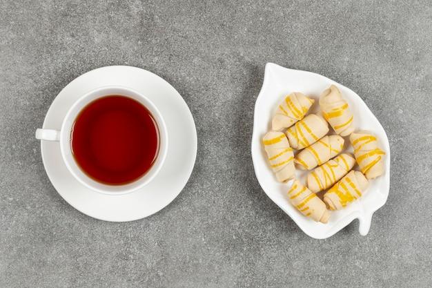 Teller mit keksen und tasse tee auf marmoroberfläche