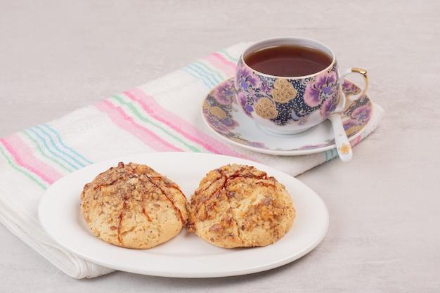 Teller mit keksen und tasse tee auf weißem tisch.