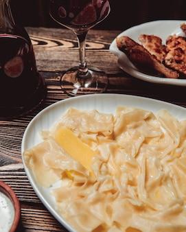 Teller mit khinkali in form von blättern und einem glas rotwein