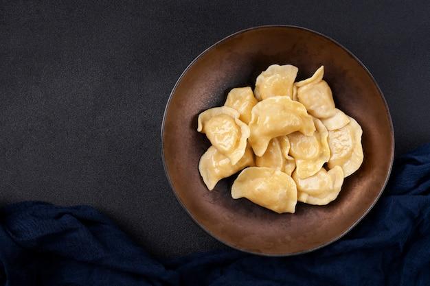Teller mit knödel namens vareniki, hergestellt aus teig mit fleisch- oder gemüsefüllung