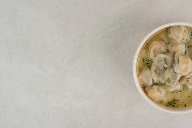 Teller mit knödeln mit gemüse auf weißem tisch.
