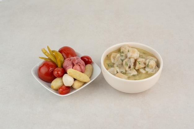 Teller mit knödeln und salzgemüse auf weißer oberfläche.