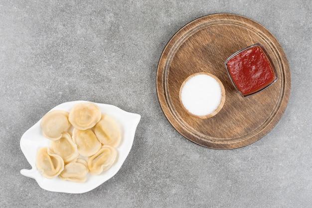 Teller mit knödeln und saucen auf marmoroberfläche