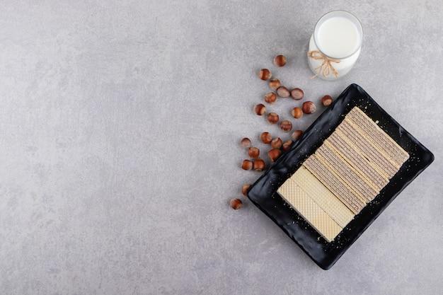 Teller mit knusprigen waffeln und frischer milch auf steintisch.