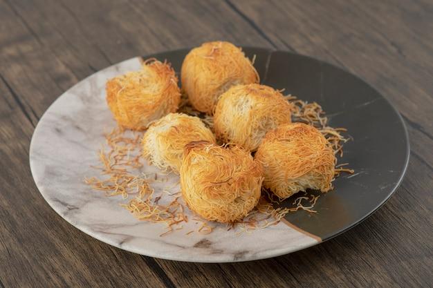 Teller mit köstlichem nestgebäck auf holztisch gelegt.