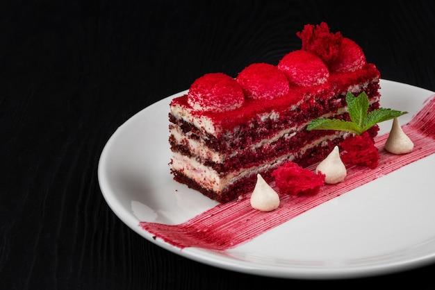 Teller mit köstlichem rotem samtkuchen auf schwarzem holzhintergrund für speisen und getränke