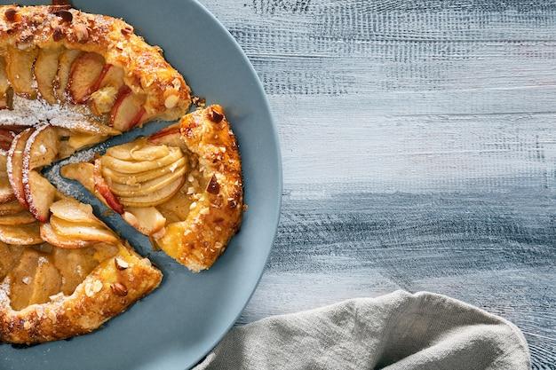 Teller mit köstlicher pfirsich-galette auf holztisch