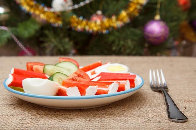 Teller mit krabbenstäbchen, gekochtem ei, frisch geschnittenen tomaten und gurken und gabel auf sackleinen, weihnachtsbaum mit spielzeugbällen und girlanden im hintergrund. feiertagstabelle.