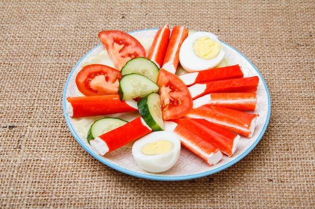 Teller mit krabbenstäbchen, gekochtem ei und frisch geschnittenen tomaten und gurken auf sackleinen. ansicht von oben.