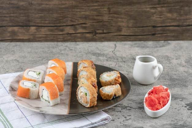 Teller mit lachs und heißen sushi-rollen mit eingelegtem ingwer auf marmortisch