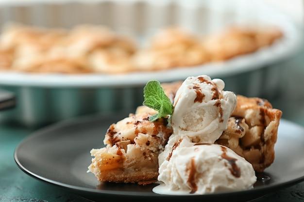 Teller mit leckerem apfelkuchen und eis auf dem tisch, nahaufnahme