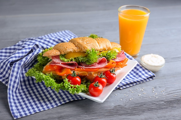 Teller mit leckerem croissant-sandwich und einem glas saft auf dem tisch