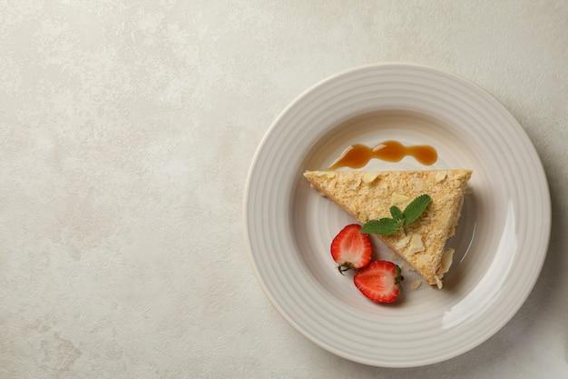 Teller mit leckerem napoleon-kuchen auf weißgrauer oberfläche
