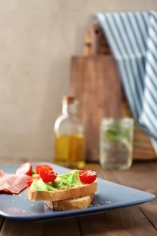 Teller mit leckerem sandwich auf dem tisch