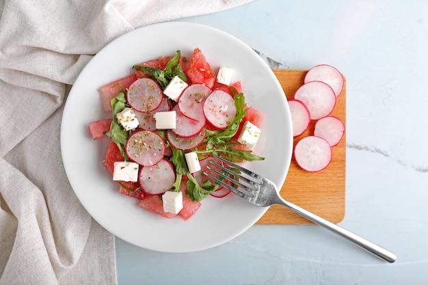 Teller mit leckerem wassermelonensalat auf dem tisch