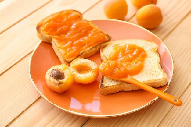 Teller mit leckeren brotscheiben und marmelade auf holztisch