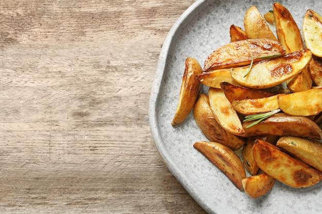 Teller mit leckeren kartoffelspalten auf dem tisch
