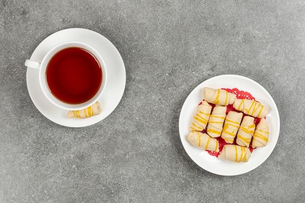 Teller mit leckeren keksen und tasse tee auf marmoroberfläche