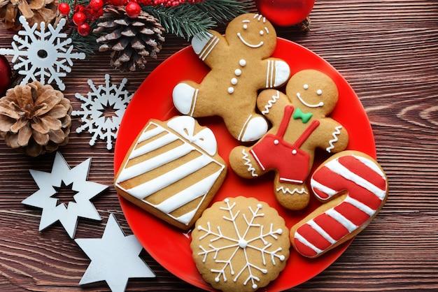 Teller mit leckeren keksen und weihnachtsdekor auf holztisch