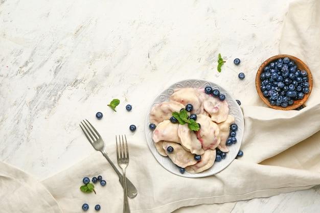 Teller mit leckeren knödeln und blaubeeren auf dem tisch