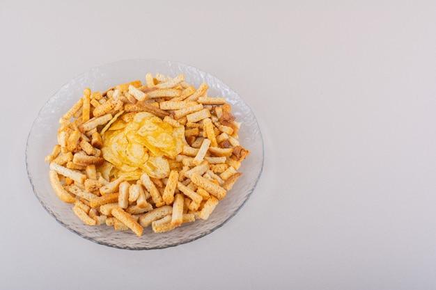 Teller mit leckeren knusprigen crackern und chips auf weißem hintergrund. foto in hoher qualität