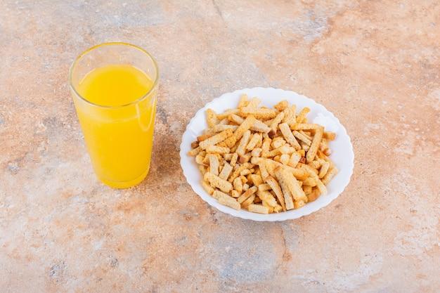 Teller mit leckeren knusprigen crackern und einem glas saft auf marmorhintergrund. foto in hoher qualität