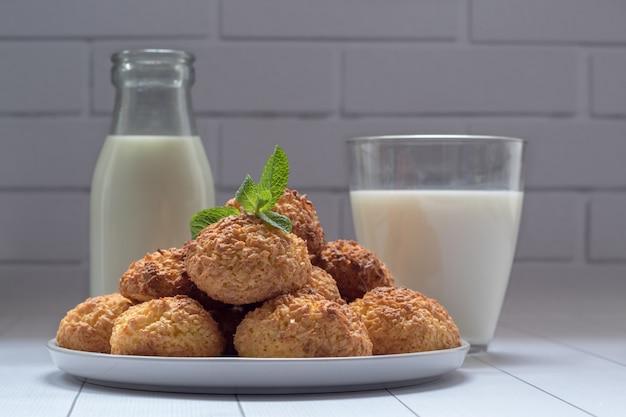 Teller mit leckeren kokosnusskeksen und milch auf weißem holztisch