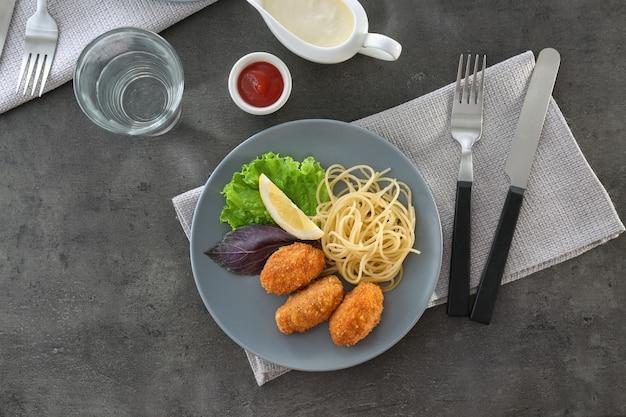 Teller mit leckeren lachskroketten und spaghetti auf dem tisch