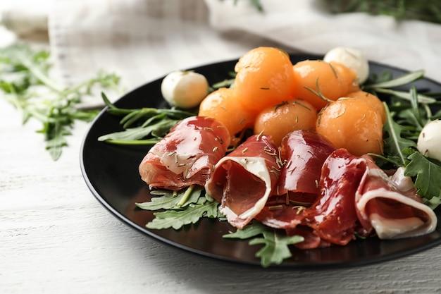 Teller mit leckeren melonenbällchen, mozzarella und prosciutto auf weißem holztisch, nahaufnahme