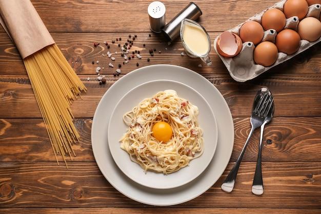 Teller mit leckeren pasta carbonara auf holztisch, ansicht von oben