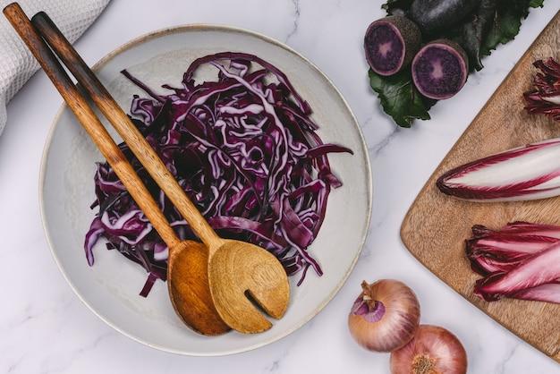 Teller mit lila rotkohl und lila kartoffel-holzlöffel