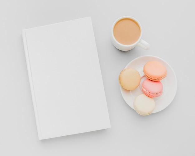 Teller mit macarons neben buch auf dem schreibtisch