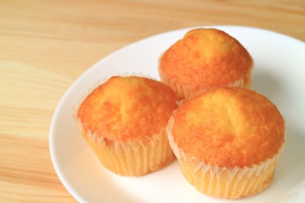 Teller mit madeleine cupcakes auf holztisch