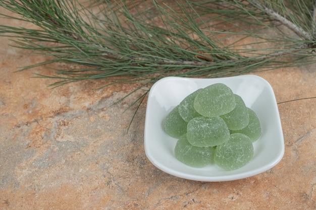 Teller mit marmeladenbonbons auf marmoroberfläche.