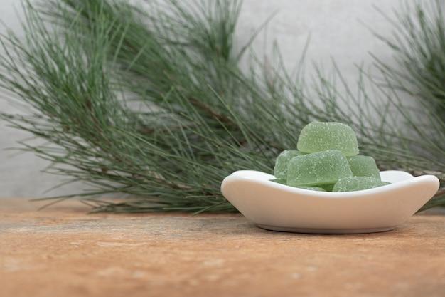 Teller mit marmeladenbonbons auf marmortisch.