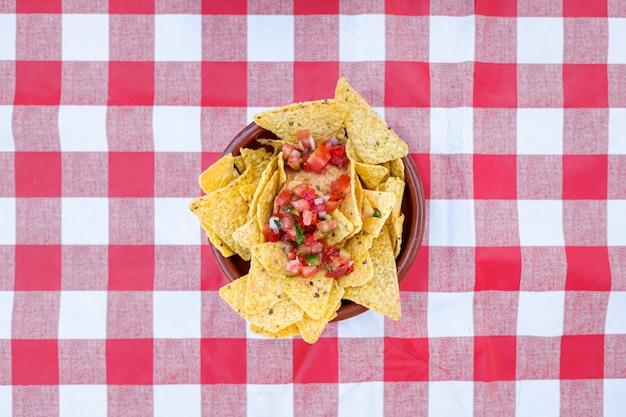 Teller mit nachos von oben auf einer rot-weiß karierten tischdecke.