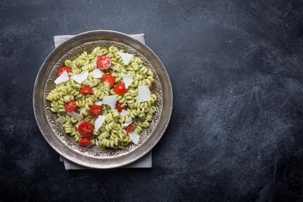 Teller mit nudel-fusilli mit pesto-sauce und kirschtomaten auf dunklem hintergrund
