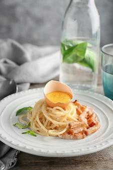 Teller mit nudeln carbonara mit speck auf dem tisch