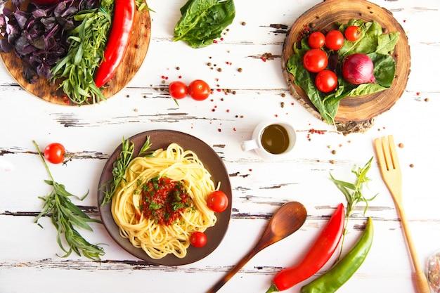 Teller mit nudeln. kirsche, chili, tomate, basilikum, gewürze, estragon, zwiebel