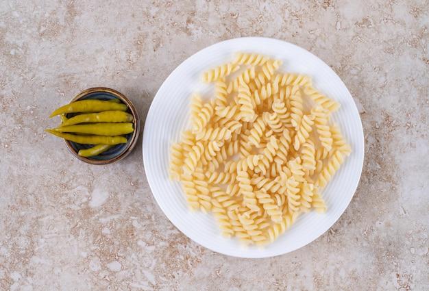 Teller mit nudeln und eine kleine schüssel mit eingelegten paprikaschoten auf marmoroberfläche
