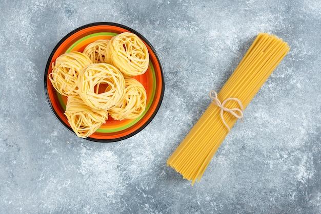 Teller mit nudeln und spaghetti auf marmorhintergrund.