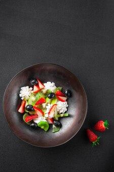 Teller mit obstsalat, kiwi, erdbeeren, blaubeeren, apfel, schlagsahne in schüssel auf dunkler oberfläche, nahaufnahme, draufsicht, ansicht von oben, layout, flach liegen, kopierraum