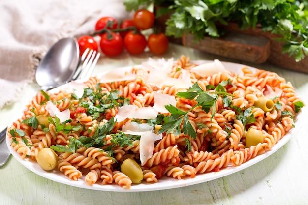 Teller mit penne-nudeln mit tomatensauce und petersilie