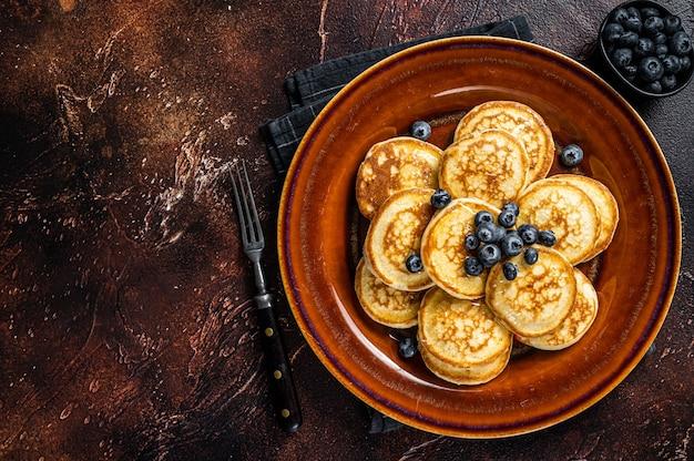 Teller mit pfannkuchen mit frischen blaubeeren und sirup. draufsicht.