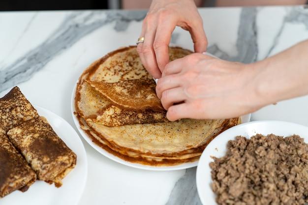Teller mit pfannkuchen und füllung und weibliche hände, die dieses gericht vorbereiten