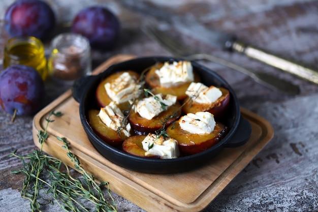 Teller mit pflaumenhälften, gebacken mit feta-käse und kräutern auf einer schäbigen holzoberfläche